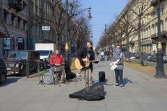 Young musicians play on the Bolshaya Konyushennaya street sunny April day. Saint Petersburg Royalty Free Stock Images