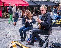 Young musicians play flute and banjo on Montmartre cobblestone street Royalty Free Stock Photos