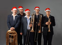 Young musicians with a wind instruments. Portrait of a five young musicians with  instruments. They are dressed in a cap of Santa Stock Images