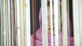 Young muslim arabian woman in pink hijab drinks cofee and looking out the window.  stock footage