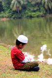 Young Muslim Boy. A Muslim boy was reading a book by the lake Stock Photography
