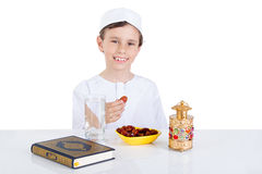 Young Muslim boy holding dates ready for brakfast in Ramadan. Sitting on a table with water , dates , Quran, and Ramadan lantern