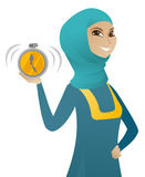 Young muslim business woman holding alarm clock. Muslim business woman showing ringing alarm clock. Young business woman holding alarm clock. Time management Royalty Free Stock Photos