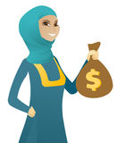 Young muslim business woman holding a money bag. Happy muslim business woman showing a money bag with dollar sign. Young successful business woman holding a Royalty Free Stock Image