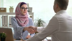 Young muslim business woman shake hands with a caucasian man during a meeting in office stock video