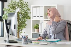 Young muslim business woman sitting in office