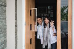 Welcoming family for eid mubarak celebration. Young muslim couple open his house front door welcoming family for eid mubarak celebration royalty free stock photography