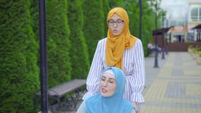 Young muslim disabled in a traditional scarf in a wheelchair communicates with a muslim friend on the street close up. Young muslim disabled in a traditional stock video footage