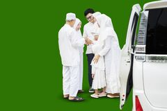 Young muslim family with kids say goodbye to their parents after Eid Mubarak celebration over green