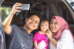 Young muslim family , transport, leisure, road trip and people concept - close up portrait happy man, woman and little girl royalty free stock images