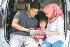 Young muslim family , transport, leisure, road trip and people concept - front view of happy man, woman and little girl sitting on stock image