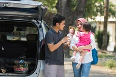 Young muslim family , transport, leisure, road trip and people concept - happy man, woman and little girl playing with doll beside royalty free stock photography