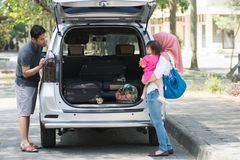 Young muslim family , transport, leisure, road trip and people concept - happy man, woman and little girl playing with doll beside royalty free stock image