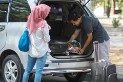 Young muslim family , transport, leisure, road trip and people concept - happy man, woman and little girl getting ready for. Young muslim family , transport royalty free stock images