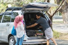 Young muslim family , transport, leisure, road trip and people concept - happy man, woman and little girl getting ready for stock photo