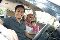 Young muslim family , transport, leisure, road trip and people concept - happy man, woman and little girl traveling inside a car stock photos