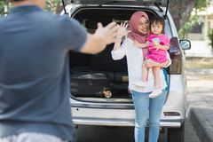 Young muslim family , transport, leisure, road trip and people concept - happy woman and little girl waving at father to say royalty free stock photo