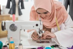 Young muslim fashion designer. Using sewing machine in her workshop Stock Photo