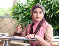 Young muslim girl with cake. On the table Royalty Free Stock Photos