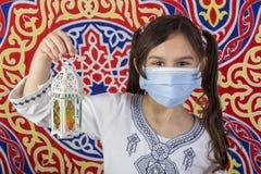 Young Muslim girl celebrating Ramadan while wearing medical mask