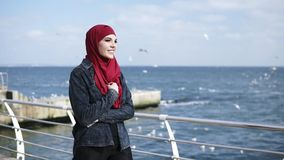 Young muslim girl enjoys walking near the seaside with seagulls flying on the background.  stock footage