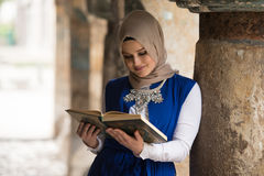Young Muslim Girl Reading The Koran Stock Images