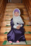 The Young Muslim Girl sits in the mosque. The young cute Muslim in the time of Ramadan is sitting in the mosque and preparing for prayer Stock Images