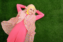 Young muslim girl wearing hijab lying on grass and looking at co. Portrait of young muslim girl wearing hijab lying on grass and looking at copy space Royalty Free Stock Image