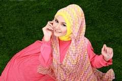 Young muslim girl wearing hijab sitting on grass and looking at Stock Photography