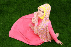 Young muslim girl wearing hijab sitting on grass Stock Images