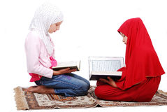 A young muslim girls in traditional clothes readin Stock Photo