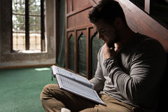 Young Muslim Guy Reading The Koran Royalty Free Stock Image