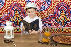 Young Muslim kid reading the holy book of Quran