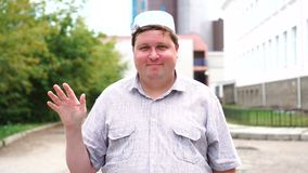 Young muslim man in city saluting by waving his hand.  stock footage