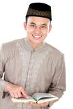 Young muslim man with finger pointing at the Quran. Portrait of handsome young muslim man with finger pointing at the Quran on white background Royalty Free Stock Photo
