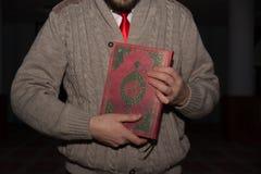 Young muslim man holding koran in hands stock image