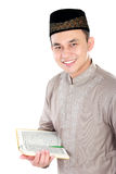 Young muslim man holding the Quran. Portrait of handsome young man holding the Quran Stock Images
