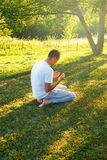 Young Muslim man pray in nature at sunset time Stock Photos