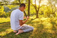 Young Muslim man pray in nature at sunset time Stock Photo