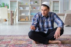 The young muslim man praying at home. Young muslim man praying at home Stock Images