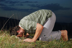 Young muslim man is praying on meadow sunset time royalty free stock images