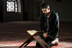 Young Muslim Man Reading The Koran Royalty Free Stock Image