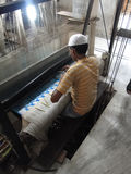 Young muslim man runs a loom to weave silk brocade Stock Images