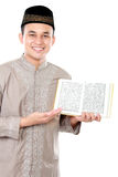 Young muslim man showing a Quran. Portrait of young muslim man showing a Quran on white background Royalty Free Stock Photos