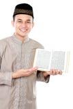 Young muslim man showing a Quran Royalty Free Stock Photos