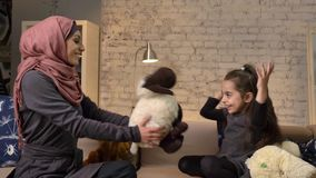 Young Muslim mother in hijab gives her daughter teddy sheep, family sitting on a sofa, idyll, home comfort in the. Background 50 fps 4k stock footage