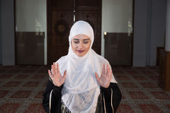 Young muslim pray in mosque. Muslim girl in mosque in tradicional islam clothes pray and reading Koran Stock Photos