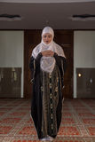 Young muslim pray in mosque. Muslim girl in mosque in tradicional islam clothes pray and reading Koran Royalty Free Stock Images