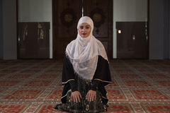 Young muslim pray in mosque. Muslim girl in mosque in tradicional islam clothes pray and reading Koran Royalty Free Stock Photography