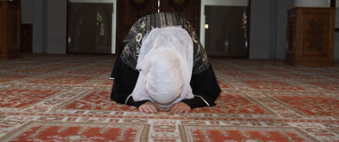 Young muslim pray in mosque. Muslim girl in mosque in tradicional islam clothes pray and reading Koran Stock Image